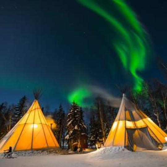 Northern Lights over teepees at Aurora Village