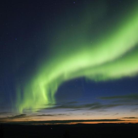 The green aurora Yellowknife Outdoor Adventures tour northern lights dancing in the sky in the Northwest Territories.