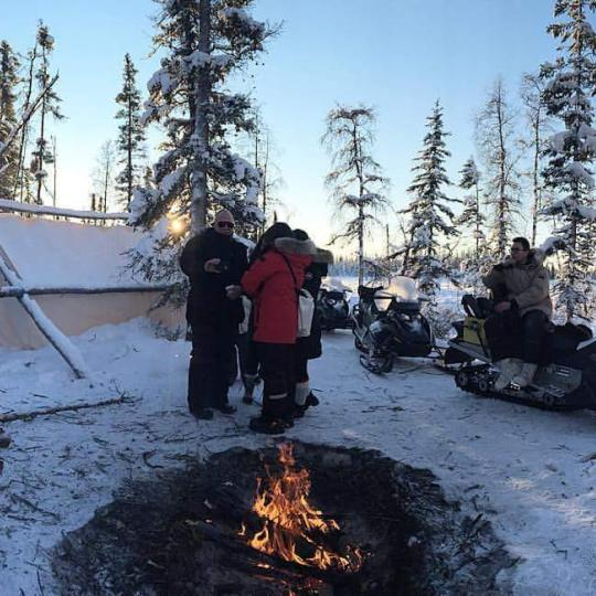North Star Adventures winter shot with a fire pit and tourists surrounded by trees in Yellowknife, NWT.