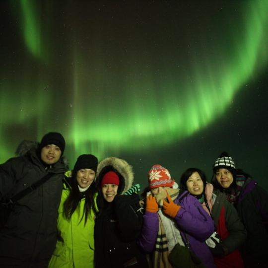 North Star Adventures group of tourists smiling with the green aurora dancing in the sky in Yellowknife, NWT.