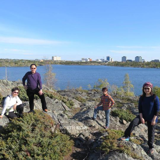 North Star Adventures four visitors posing in the canadian shield in Yellowknife NWT.