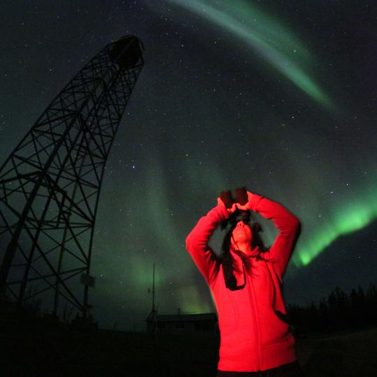 Person with their arms up in the air watching the Aurora borealis over Fort Smith, NWT.
