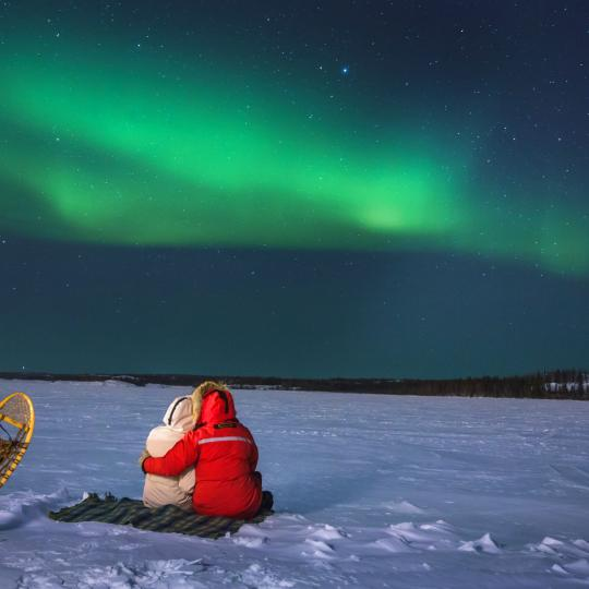 man and snowshoes under aurora