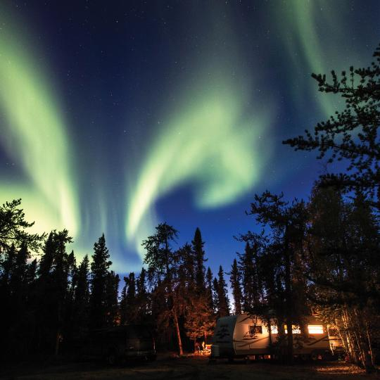 Northern Lights shining atop the trees at a camping lodge