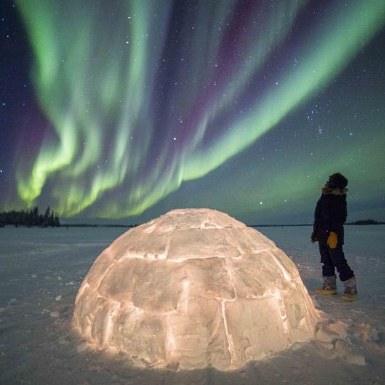 multicolored northern lights over glowing igloo