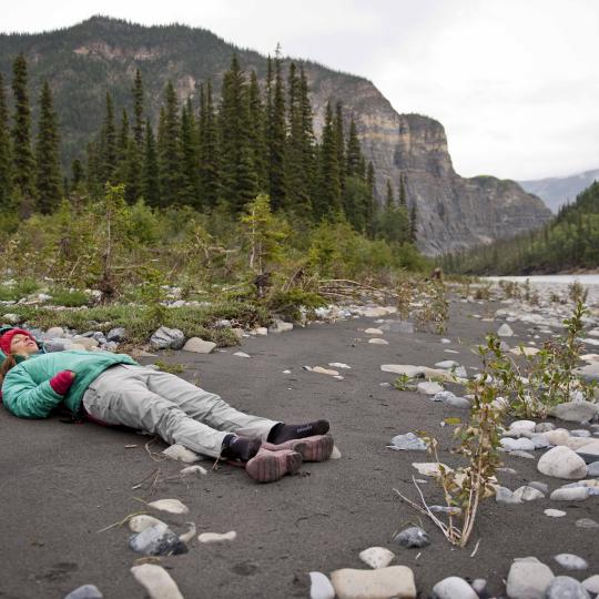 Person laying on their back on the muddy ground by the shore of the Mackenzie River taking a break after a long day of canoeing