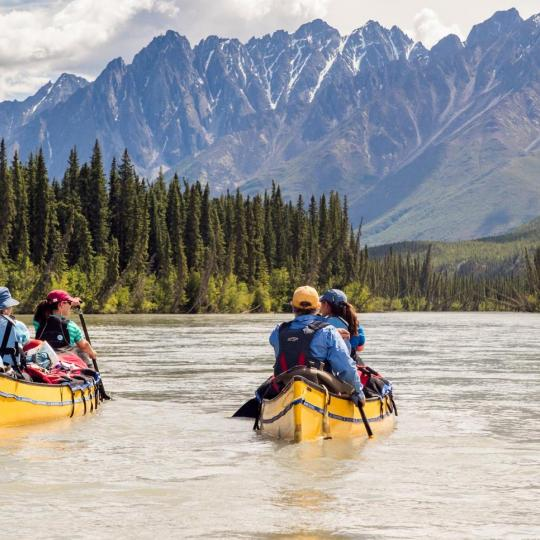 Yellow canoes float on the water with people paddling on an amazing canoe trip in Nahanni National Park Reserve, NWT