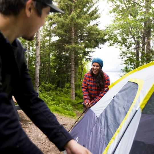 a couple sets a tent up together at a northwest territories campsite