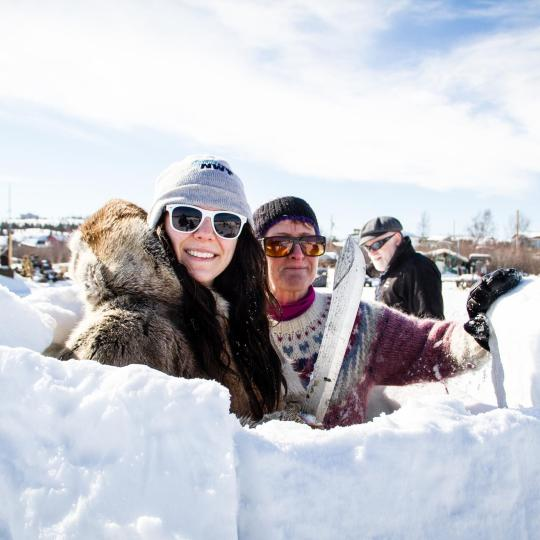 two people have a blast building an igloo