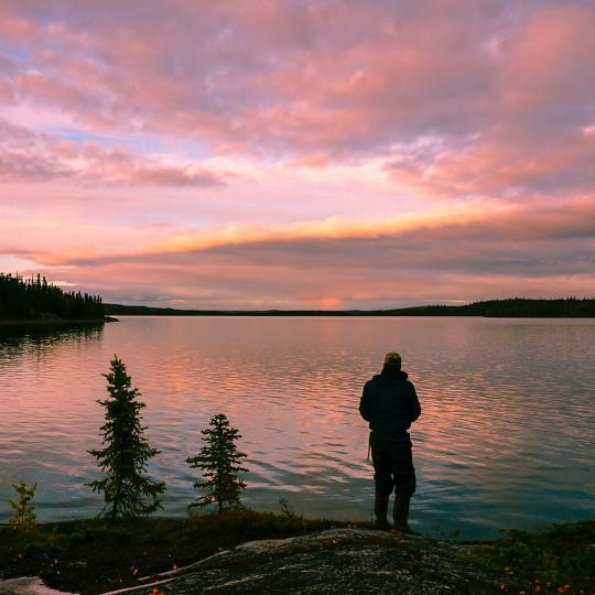 A person stares into the lakeside view under the midnight sun in the NWT