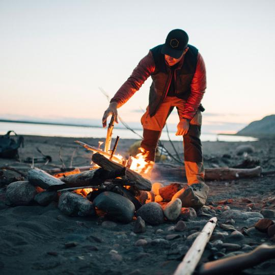 A person tends to a fire on a beach in the Northwest Territories