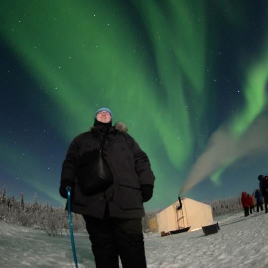 A persons stands under the Winter Aurora dancing in the sky