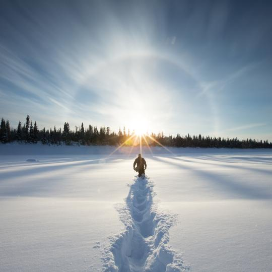 a person hikes through the snow towards the sun in the Northwest Territories