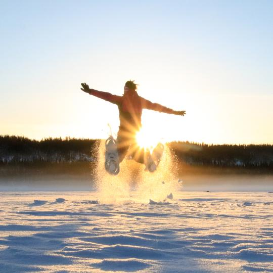 A person enjoys a snowshoe in the setting sun on a frozen lake in Wood Buffalo National Park, NWT