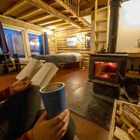 A person reads a book at a cozy cabin at Blachford Lake Lodge in the NWT