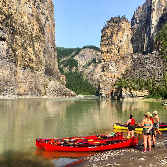 A group of people dock their canoes on the shoreline in Nahanni National Park NWT