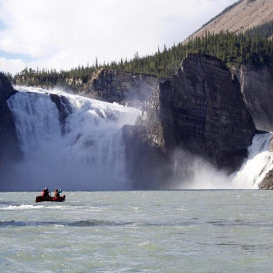 Nahanni National Park water fall with two paddlers Nahanni Wild in the Dehcho Northwest Territories.