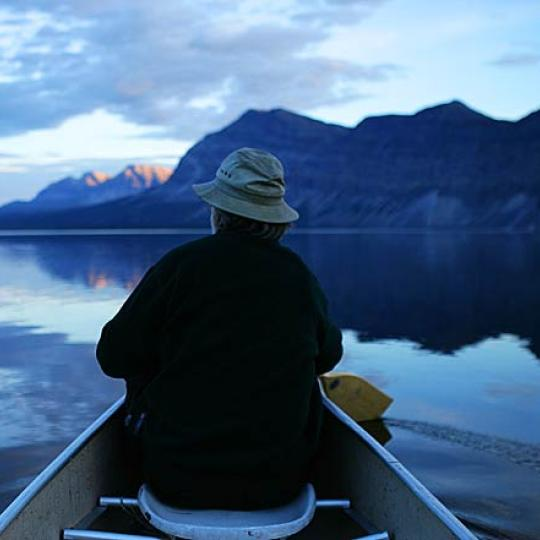 Simpson Air a man paddling in the Nahanni National Park with the mountains in the back at dawn in the NWT.