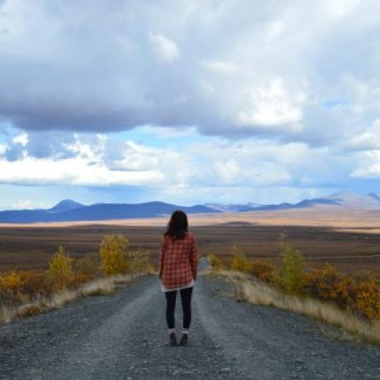 A woman standing on the Dempster Highway on a cloudy day in the Western Arctic , NWT.