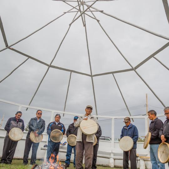 Sahtu Adventures group of Indigenous people holding drums in a ceremony in the Northwest Territories.