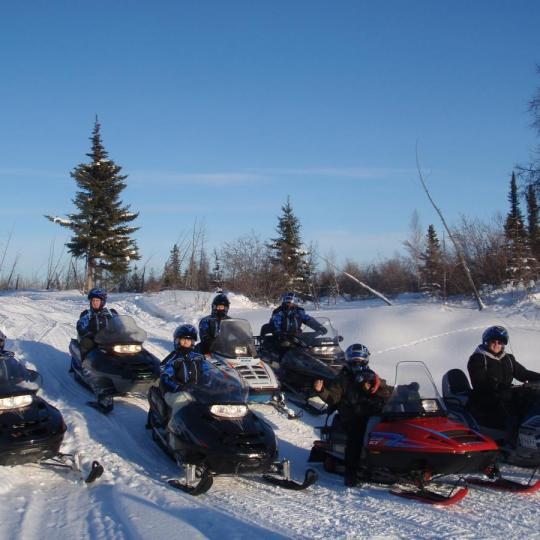 Seven tourists on a Yellowknife Outdoor Adventures snowmobile tour on the Great Slave Lake in winter in Yellowknife, NWT.