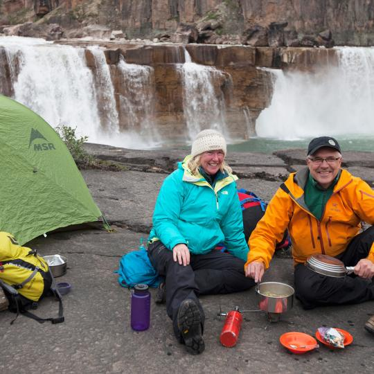 couple camping by waterfall