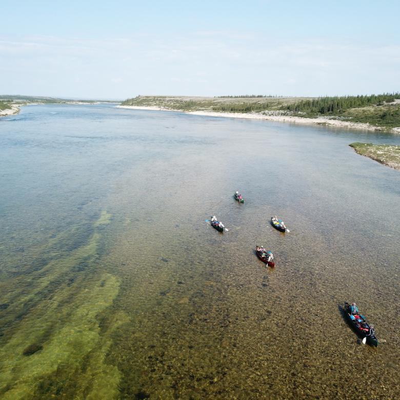 An over head shot of five canoes with people paddling on a Jackpine Paddle - Thelon River trip.