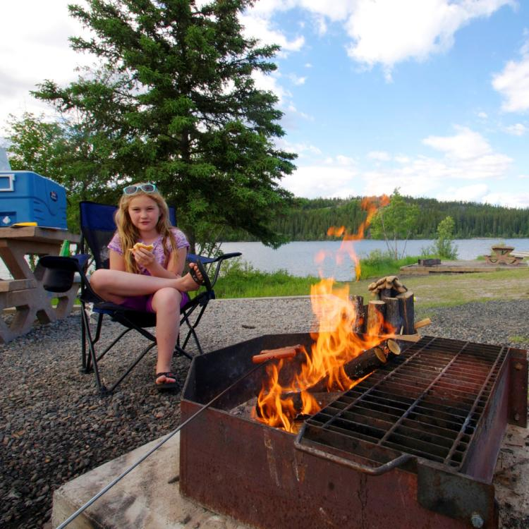 a youth sits at a fire pit at Madeline Lake Park Day use area in the N.W.T.