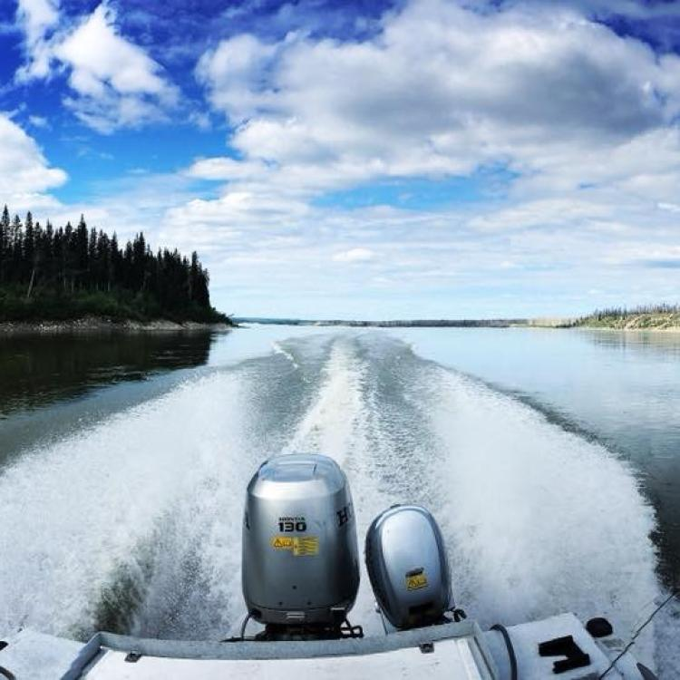 North Star Adventures water trail of a speed boat on the Mackenzie River in the Dehcho Region in NWT.