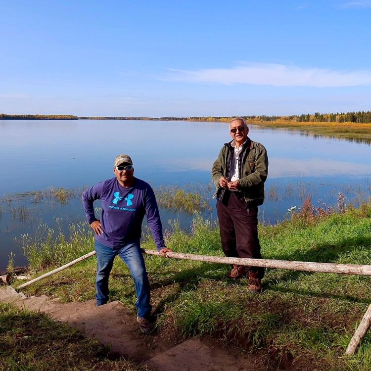 Joe Bailey of North Star Adventures stands beside an elder next to a lake in the NWT