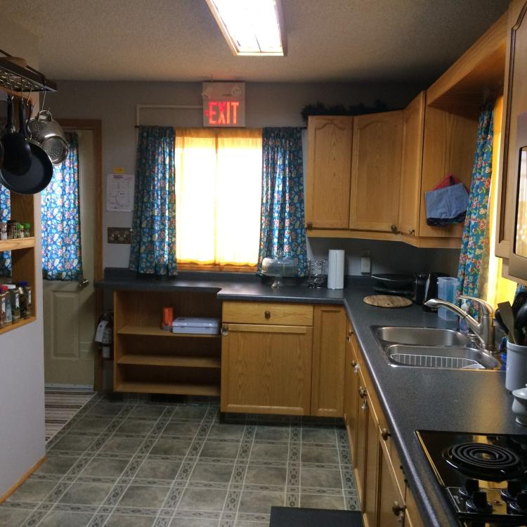Tiga Bed and Breakfast kitchen  area with sink, stove, and counter top in Yellowknife, NWT.