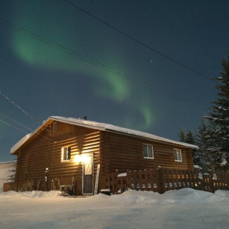 Our Cabin B&B on Ragged Ass Road in winter surrounded by snow and swirling green aurora in the sky in Yellowknife, Northwest Territories.