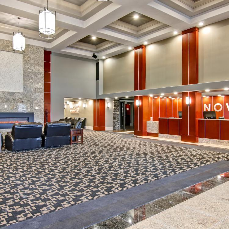 Nova Hotel Yellowknife brightly lit lobby with black leather couches and fireplace in the Northwest Territories.