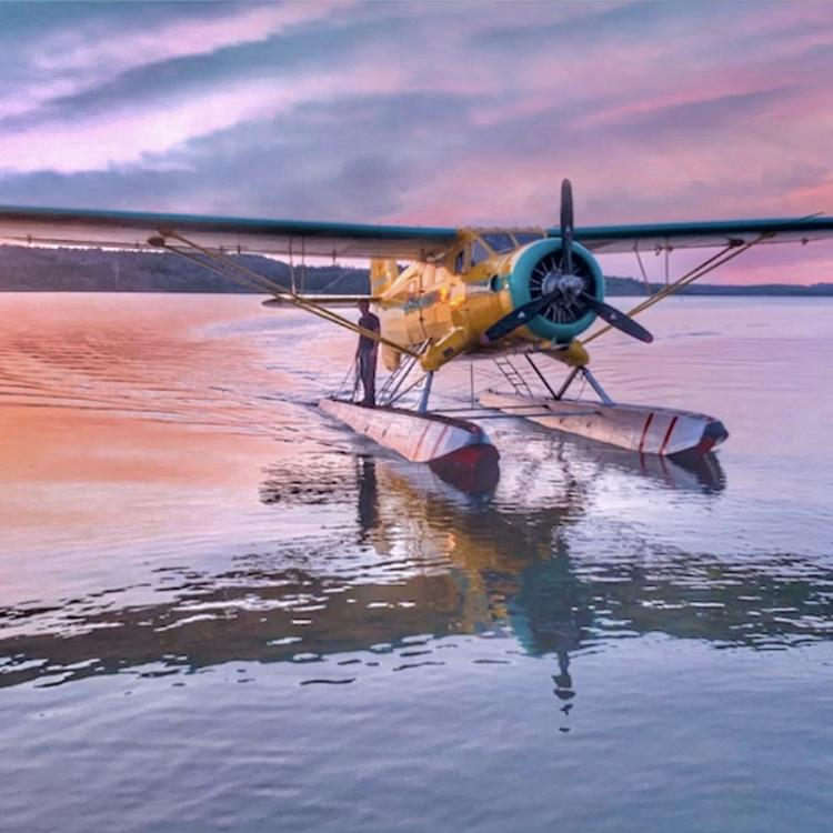 Buffalo Airways float plane resting on the water as the sun sets behind it in the orange and blue cloudy sky in the Northwest Territories.
