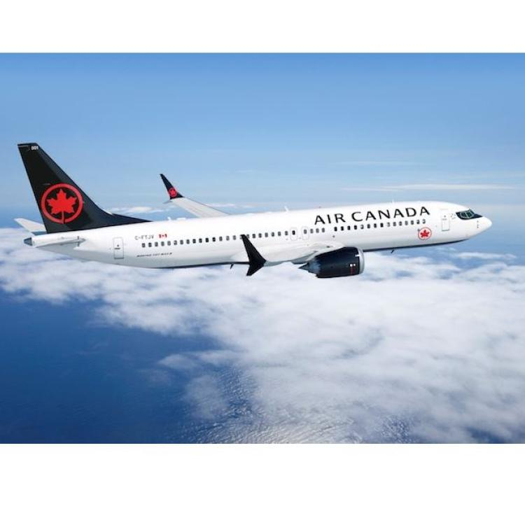 Air canada max 8 airplane flying in the sky above the clouds on a sunny day.