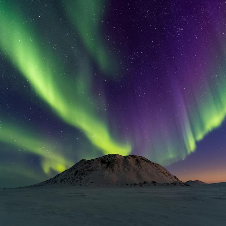 the northern lights dance above a pingo in the Northwest Territories