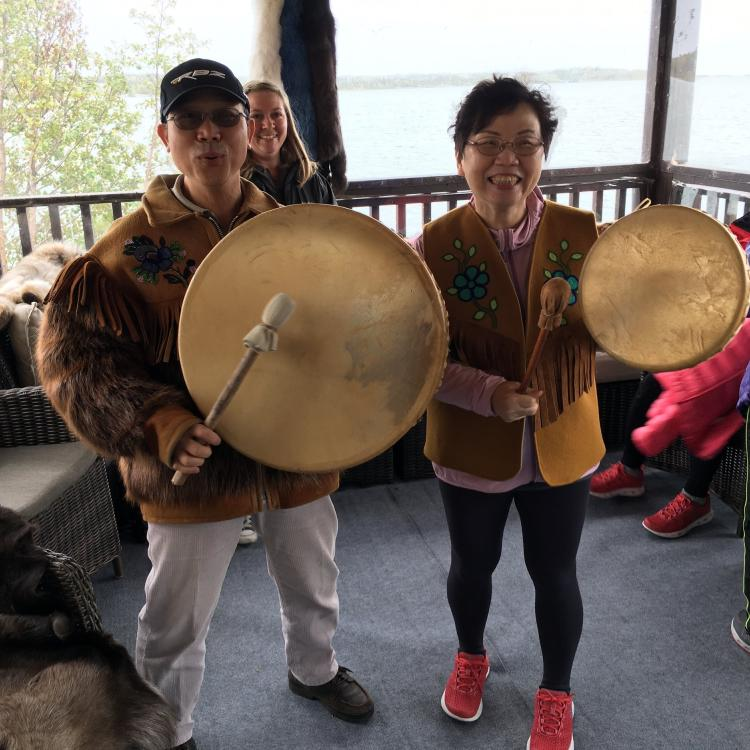Aurora Tours.net Asian couple people on an indigenous cultural tour drumming in Yellowknife, NWT.