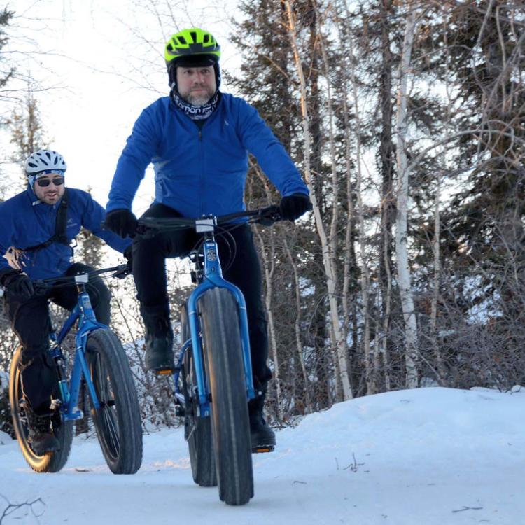Borealis Bike Tours Unlimited two men riding a fat bike on a snowy trail in the winter in Yellowknife Northwest Territories.