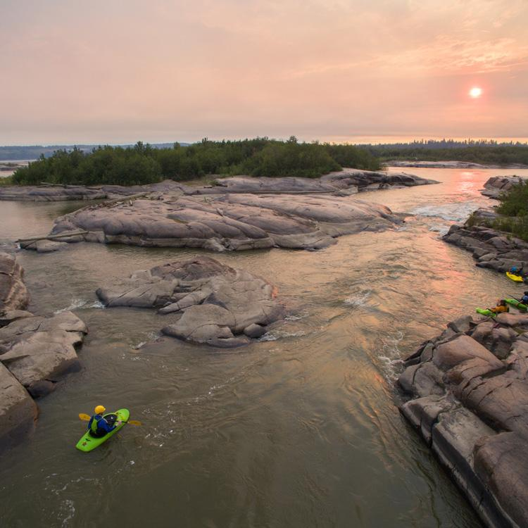 A paddler kayaking the Slave River at sunset in the town of Fort Smith in the Northwest Territories.