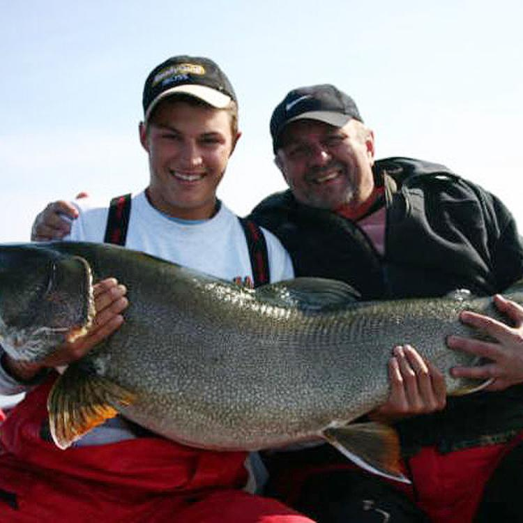 Two men at Plummer's Trophy Lodge holding a huge trophy fish caught in the Great Bear lake in teh Northwest Territories.