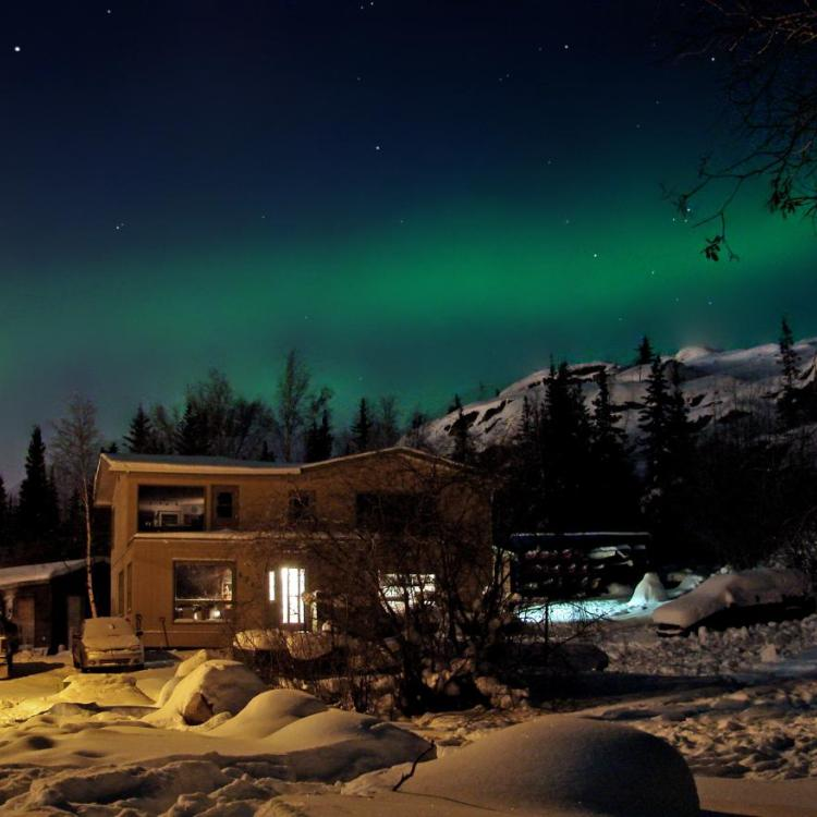 Narwal Northern Adventures building with the green aurora in the night sky in winter in Yellowknife Northwest Territories.