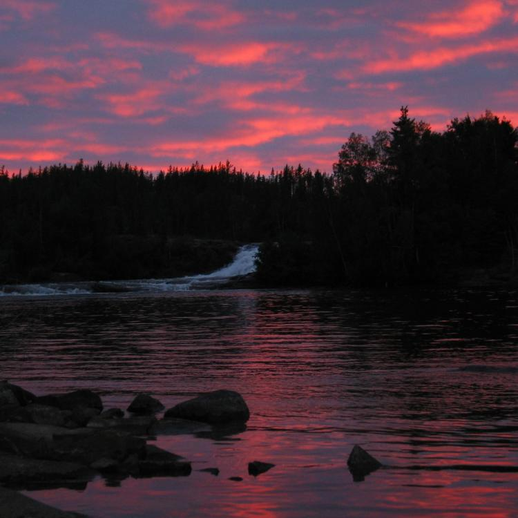 Beautiful sunset over the waterfall at Watta Lake Lodge in the NWT