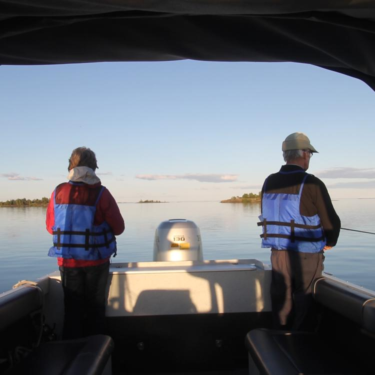 Two people backs turned on a North Star Adventures fishing experience on the Great Slave Lake in the NWT.