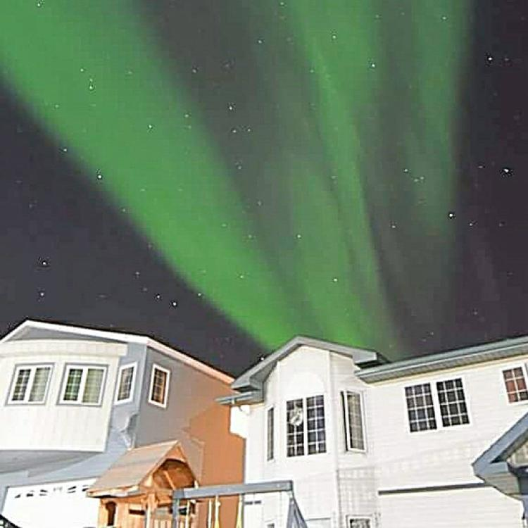 A stream of green aurora over Northern Star B&B and Tourism Services in fall in Yellowknife NWT.