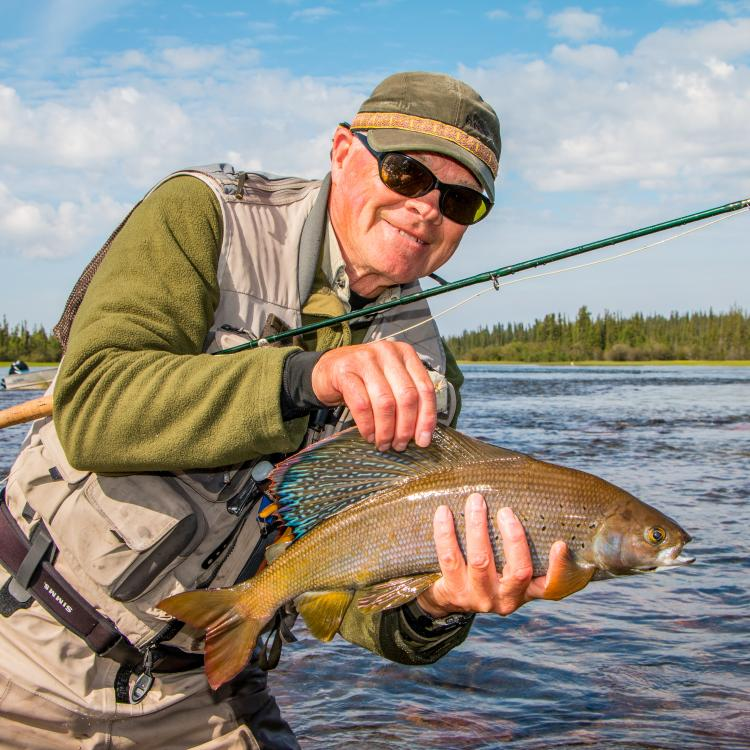 Arctic Grayling held up by a fisher caught at Frontier Fishing Lodge on a sunny day.