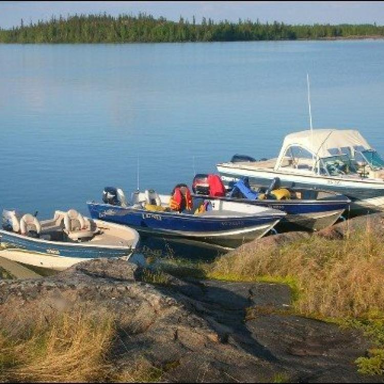 Bluefish Services beautiful sunny day three boats docked on the Great Slave Lake in Yellowknife Northwest Territories.