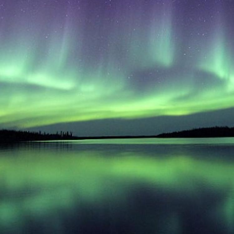 Nanook Aurora Tours green and purple aurora dancing in the sky over a large lake in Yellowknife, Northwest Territories.