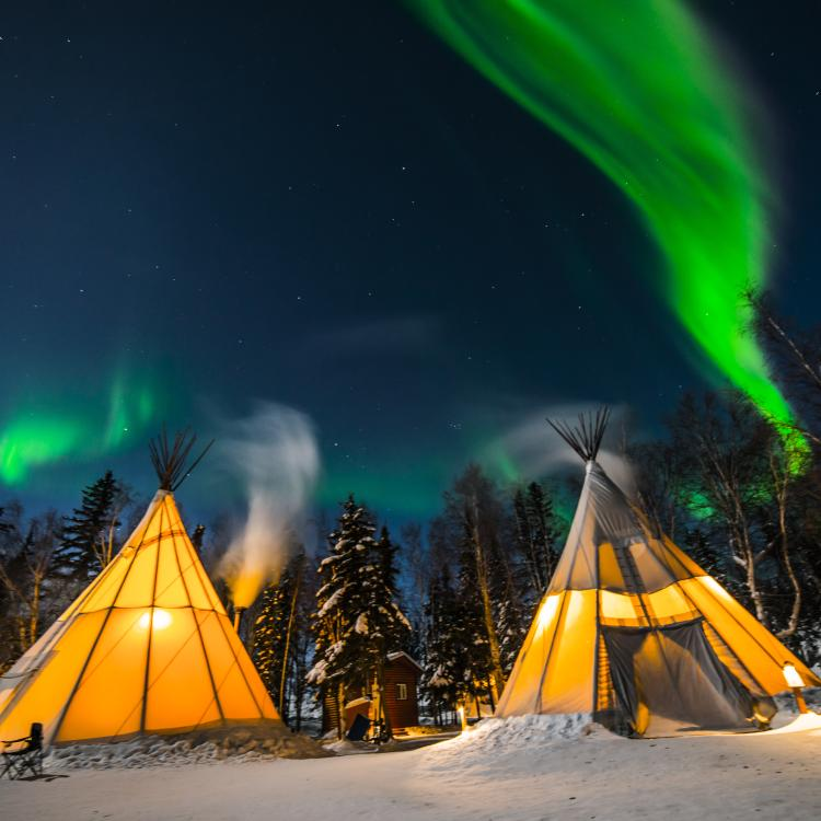 Aurora Village glowing teepee experience at night with the green aurora dancing in the sky in Yellowknife, NWT.