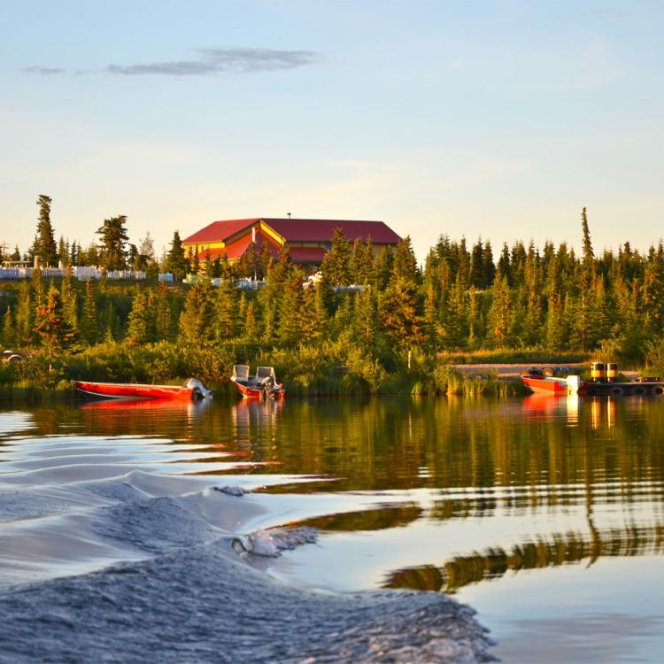 Grey Goose Lodge exterior picture surrounded by trees and the Great Bear Lake at sunset in Deline in the Northwest Territories.