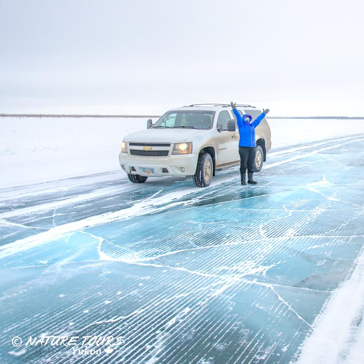 Nature Tours of Yukon a man by his parked car on an ice roads in the western arctic Northwest Territories.